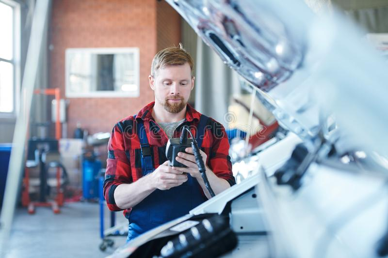 Using electronic device. Young contemporary technician or repairman in workwear looking at data in electronic device while standing by one of cars royalty free stock image