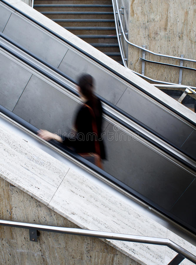 Using escalators. A person in motion blur is using the escalators next to regular stairs stock image