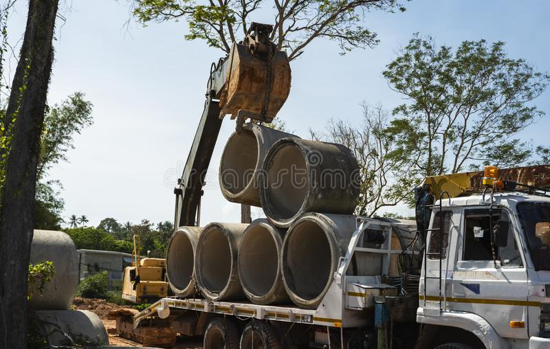 Using an excavator to transfer large pipes to a vehicle. royalty free stock image