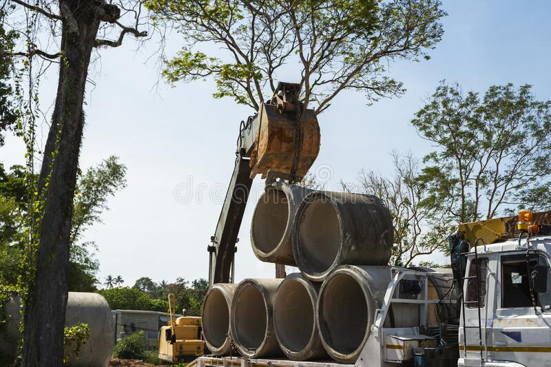 Using an excavator to transfer large pipes to a vehicle. Using an excavator to transfer large pipes to a vehicle royalty free stock photos