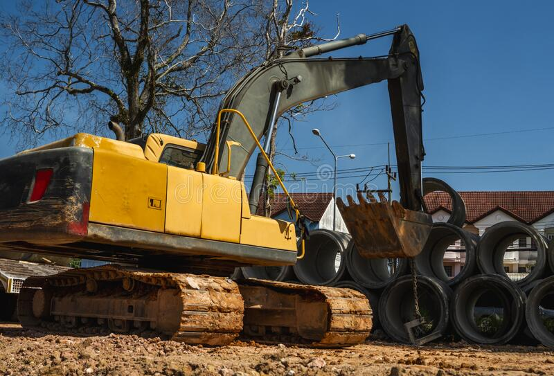 Using an excavator to transfer large pipes to a vehicle. Using an excavator to transfer large pipes to a vehicle stock images