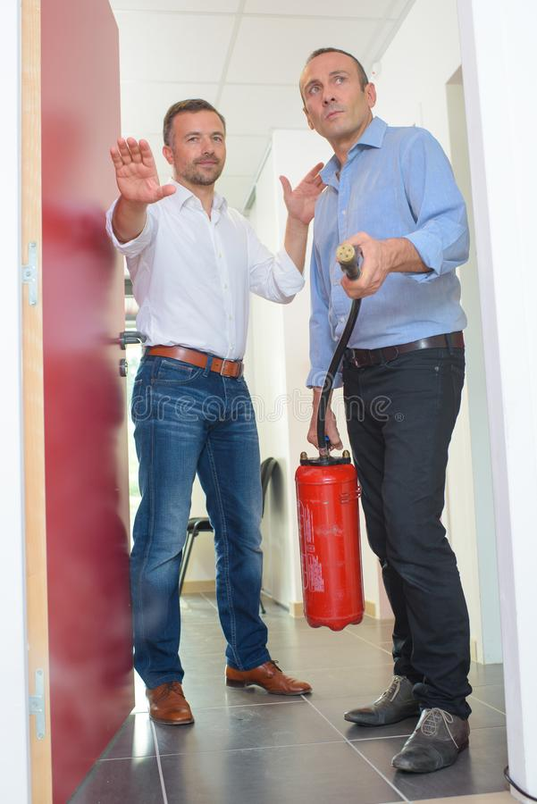 Using fire extinguisher in office stock photos