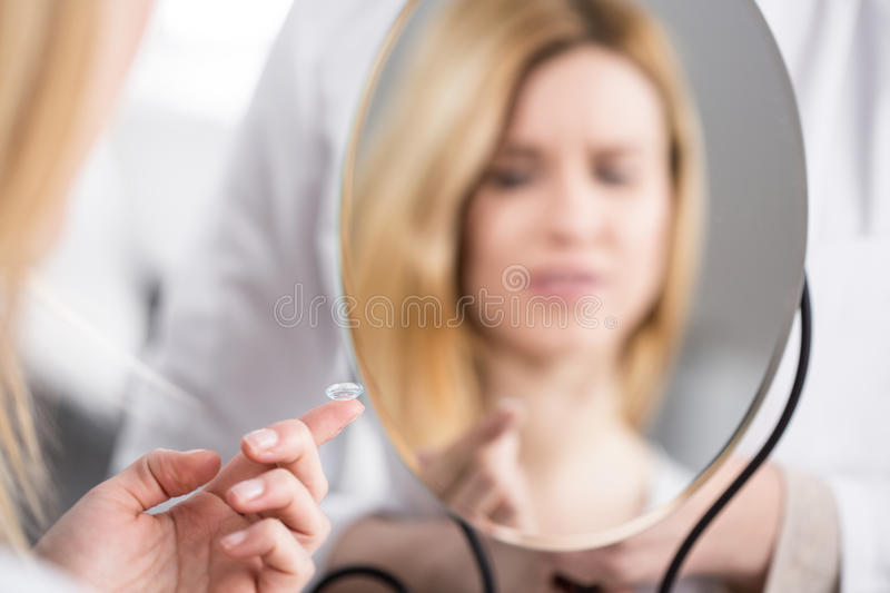 Using first time contact lenses. Young women using first time contact lenses stock photo