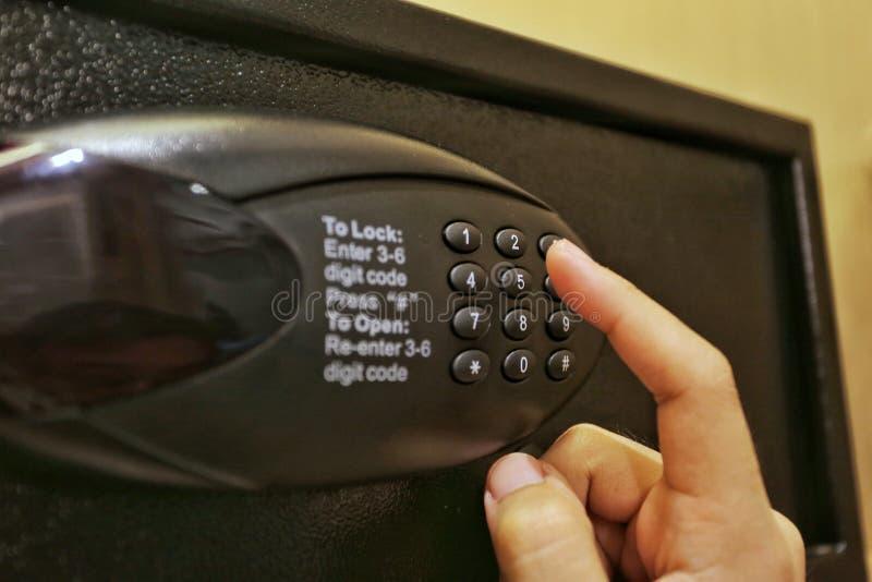 Using forefinger / index finger pushing number button on black safe to unlock safe or set password for safe. Using forefinger / index finger pushing number royalty free stock photos