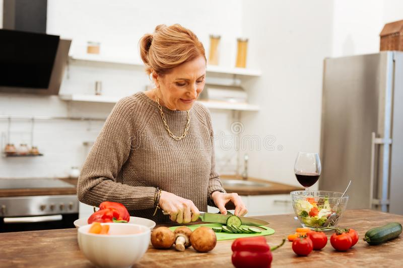 Concentrated mature woman getting dinner ready on wooden table. Using fresh vegetables. Concentrated mature woman getting dinner ready on wooden table while royalty free stock photo