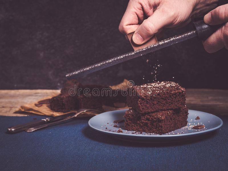 Using a grater or rasp to decorate brownies with chocolate stock photo