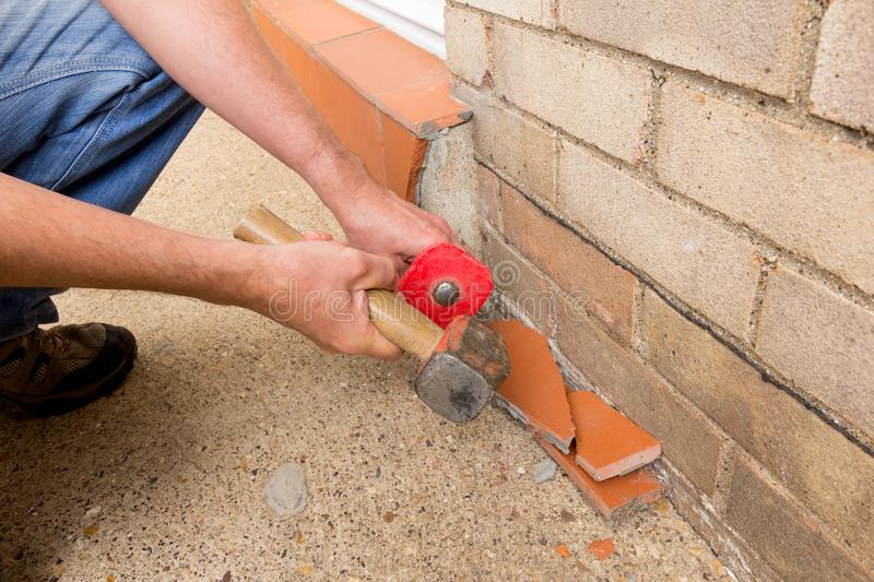 Using a hammer and bolster to remove tiles. Man using a hammer and bolster to remove terracotta tiles from a doorstep stock photo