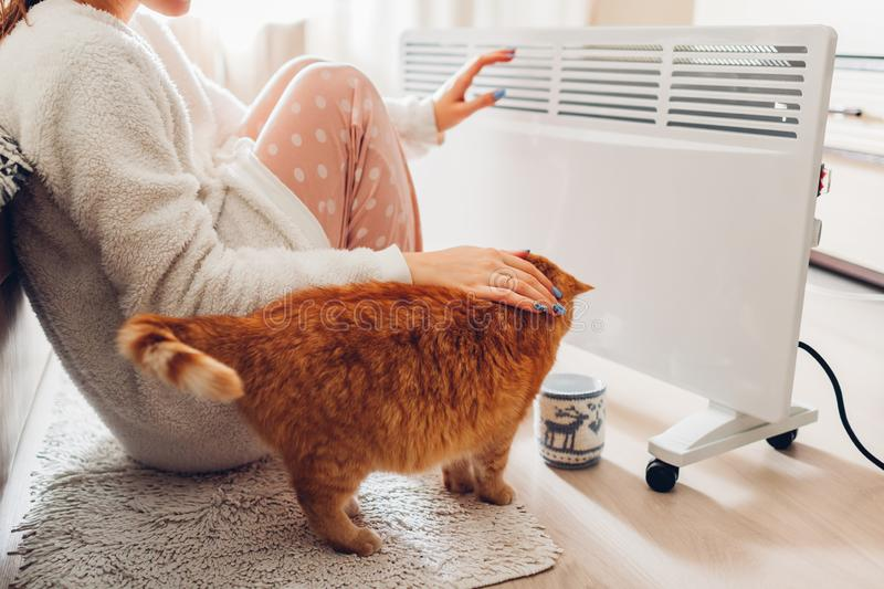 Using heater at home in winter. Woman warming her hands with cat. Heating season. Using heater at home in winter. Woman warming her hands sitting by device with royalty free stock photography
