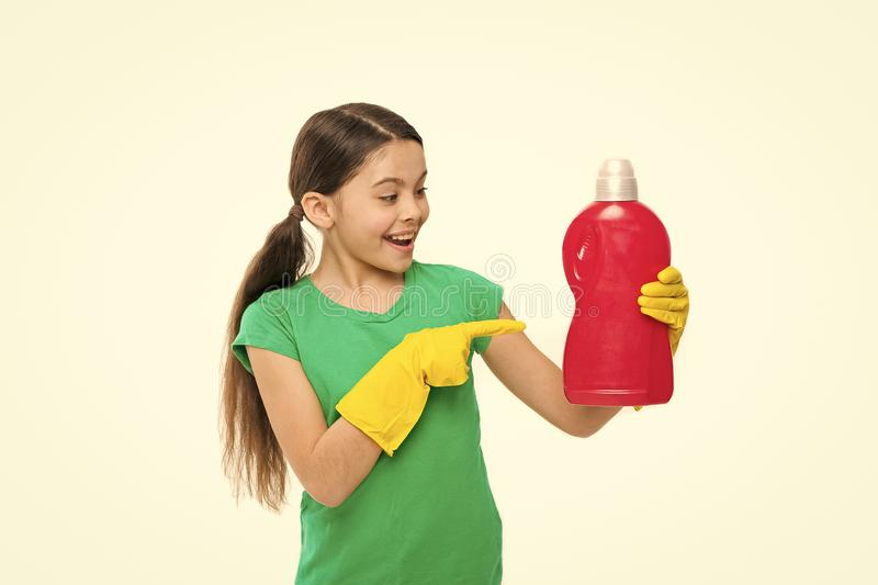 Using household cleaning product. Small housekeeper pointing at detergent bottle. Little child enjoy doing laundry. Cute. Household helper wearing rubber gloves stock image