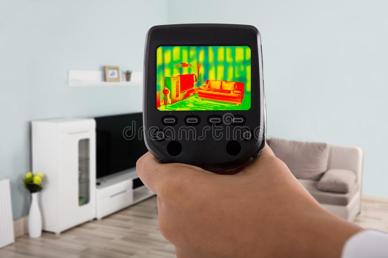 Using Infrared Thermal Camera In Living Room. Person Hand Using Infrared Thermal Camera In Living Room stock images