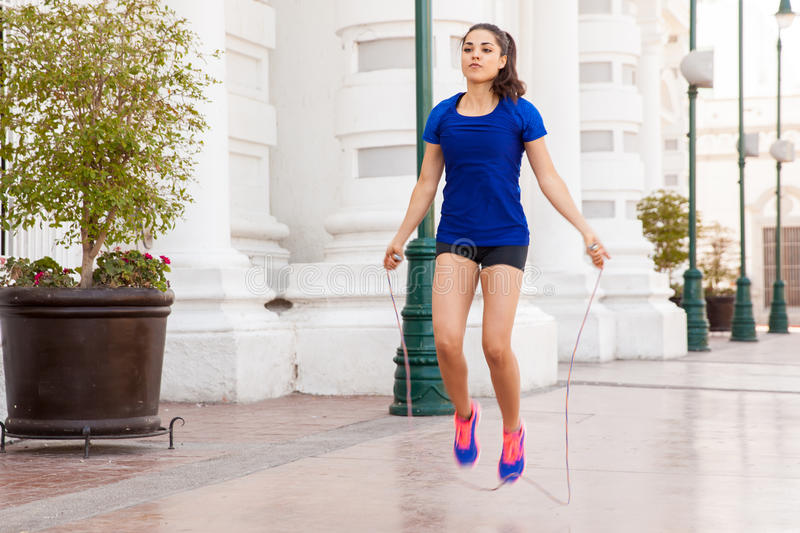 Using a jump rope in the city. Pretty girl in sporty outfit working out and using a jump rope outdoors royalty free stock image