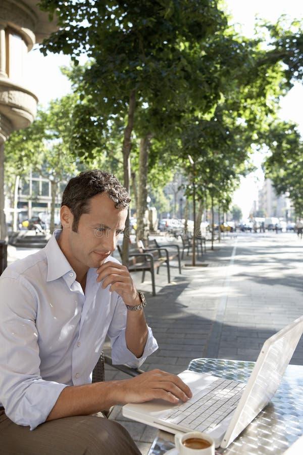 Using Laptop At för fundersam affärsman utomhus- kafé arkivbilder