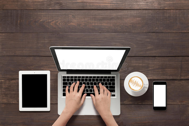 Using laptop, tablet, smartphone and a cup of coffee on wooden b. Ackground stock image