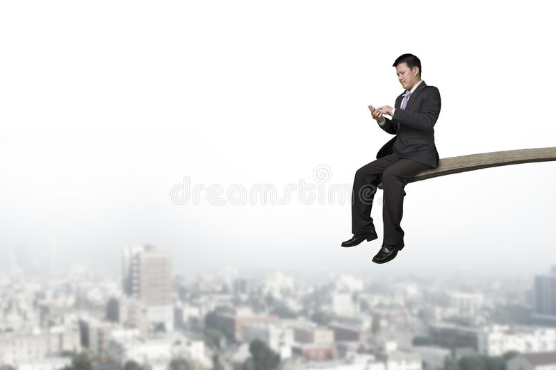 Using mobile phone businessman sitting on springboard with cityscape royalty free stock photo
