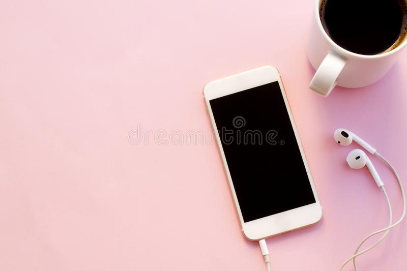 Using mobile phone holding coffee cup. royalty free stock photo