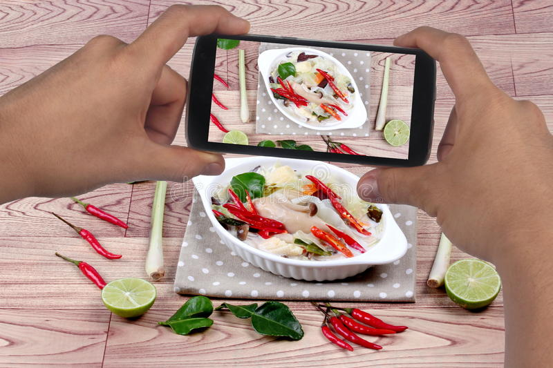 Using mobile phone to take photo a dish of spicy and sour galangal curry with mixed herb for share to social network. Selective. Spicy and sour galangal curry stock photography