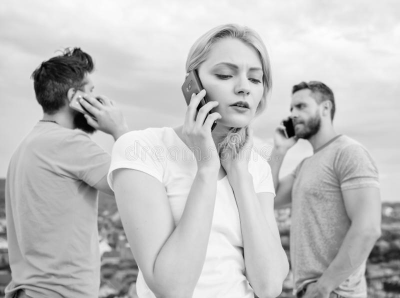 Using the mobile technology while on the move. Group of friends talk on cell phones. Modern people with smartphones royalty free stock photos