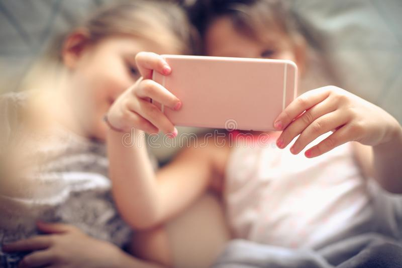 Using mobile together. Two little girl using smart phone together. Close up. Focus is on hands stock images