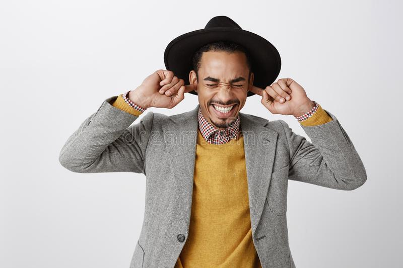 Using natural earplugs not to hear spoilers. Good-looking happy dark-skinned guy in classy hat and stylish outfit royalty free stock photography