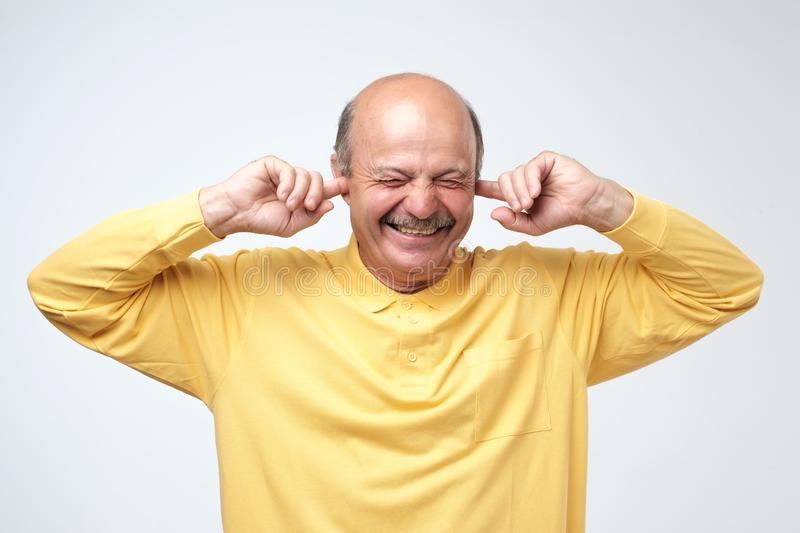 Using natural earplugs not to hear spoilers. Good-looking happy mature european man smiling with closed eyes royalty free stock image