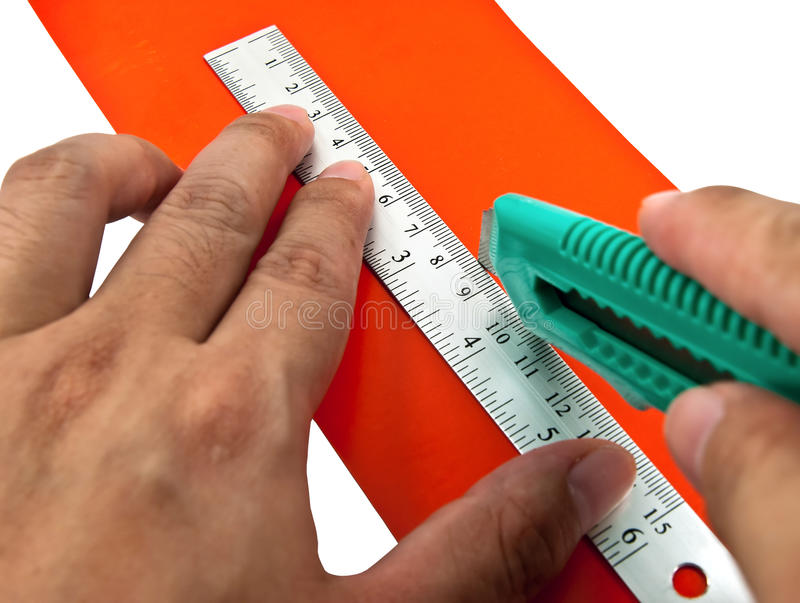 Using office tools. Hand holding a cutter and ruler cutting red paper stock images