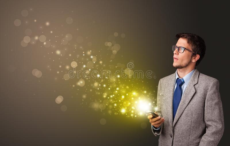 Using phone with gold sparkling concept royalty free stock photography