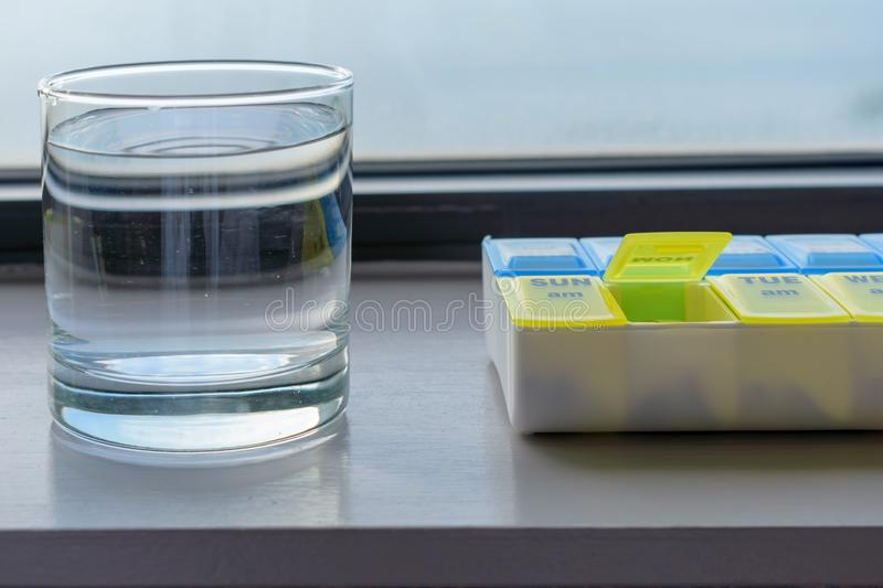 Using a pill holder for daily medication royalty free stock photo