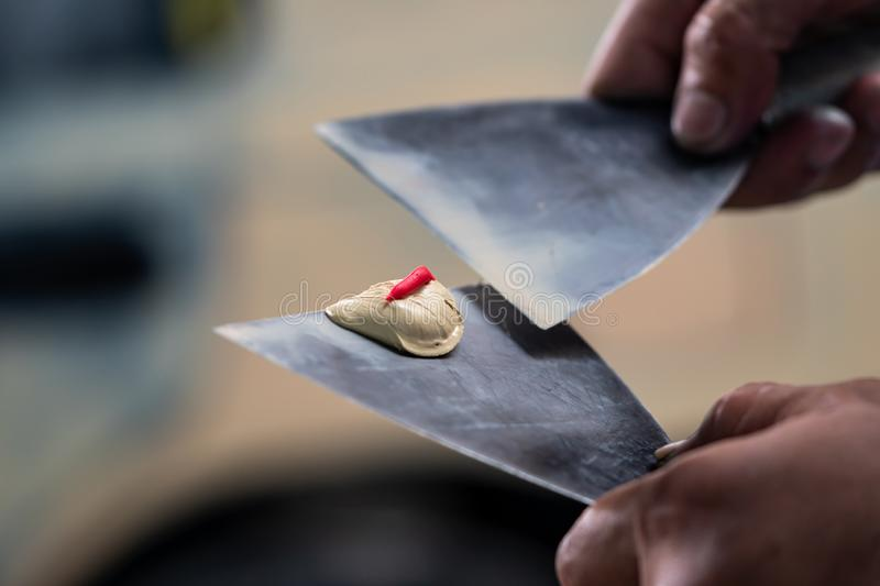 Using plastic putty ,Prepare surface for spray painting. Repairing car body by puttying close up work after the accident by working sanding primer before stock photos