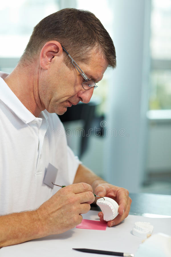 Using a probe on dentures. Dental technician working on dentures with a probe royalty free stock photos