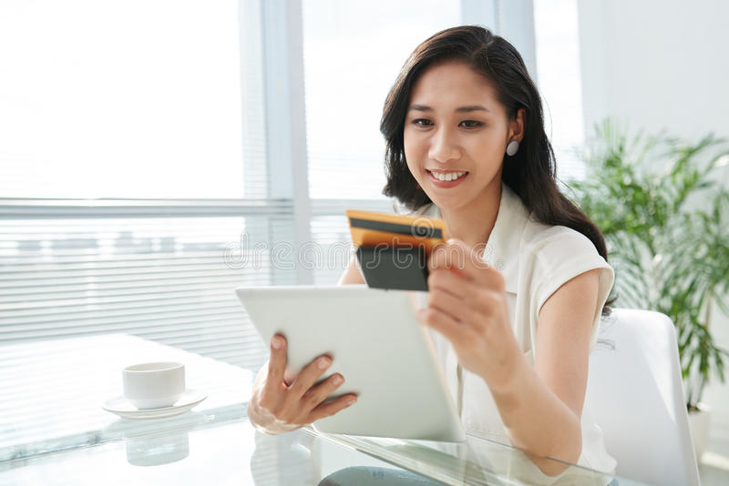 Using reading device. Portrait of pretty Vietnamese woman using reading device attached to digital tablet stock image