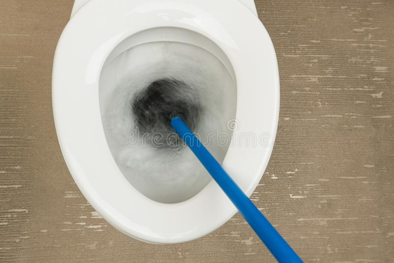 Using the rubber plunger to unclog. The flush toilet stock photo
