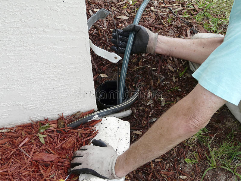 Using Sewer Rod to Clear Blockage. Homeowner uses sewer snake or rod to clear a blockage of dirt and leaves in the PVC pipe out to a point where water can be royalty free stock photography