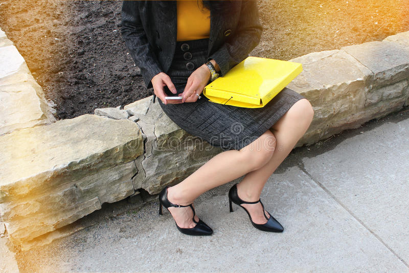 Using smart-phone. Elegant business woman, with a notebook in her lap, sitting on a stone fence and sending a message. Business woman using her smart-phone