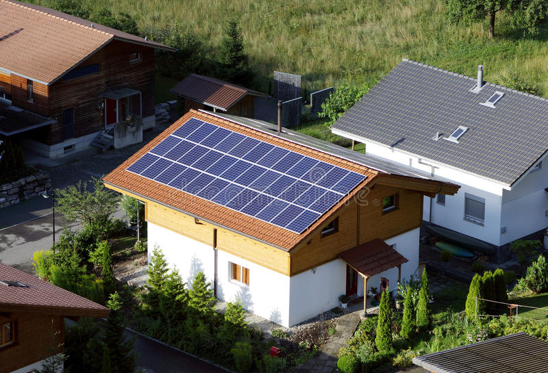 Using solar energy is money saving as well as environmental friendly power generation. INTERLAKEN, SWITZERLAND - JULY 25: A house in Interlaken city with solar royalty free stock image