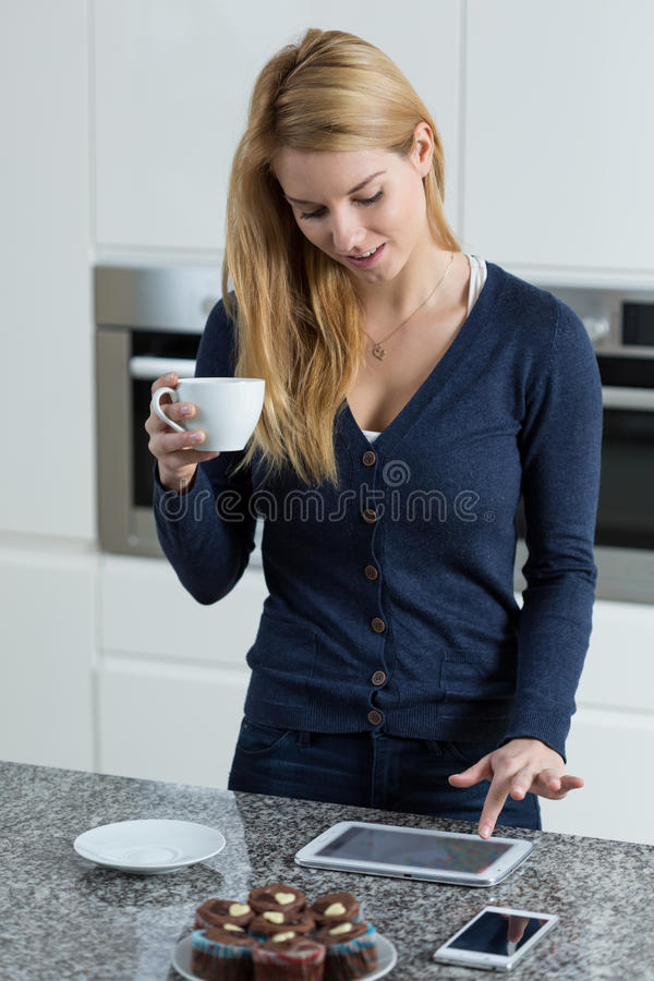 Using tablet during drinking coffee royalty free stock photo