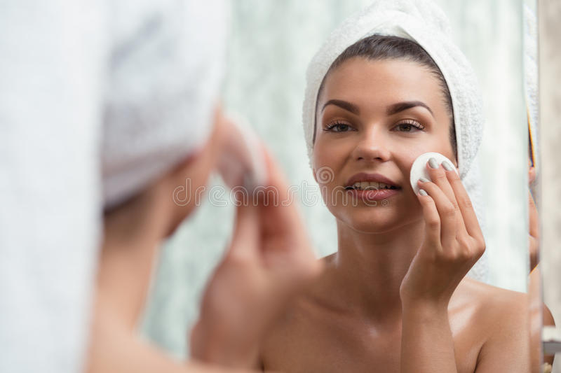 Using a toner. Young woman is using a toner for her complexion stock images