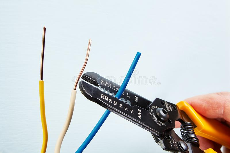 Using wire stripper cutter during electrical wiring installati. Electrician uses wire stripper tool during electrical wiring services stock image