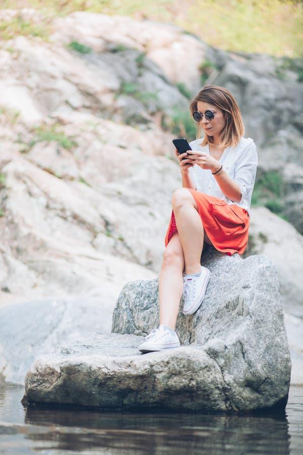 Usinsmartphone för ung kvinna på sjön fotografering för bildbyråer