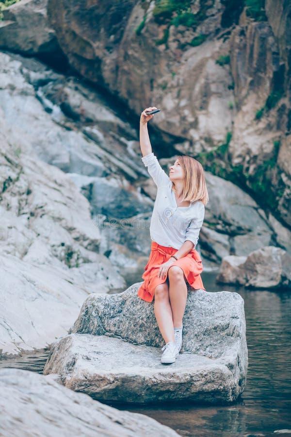 Usinsmartphone för ung kvinna på sjön royaltyfri bild