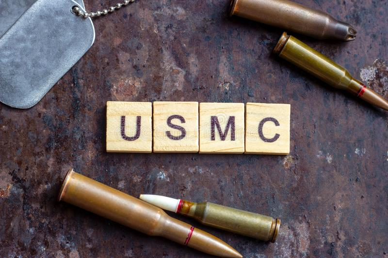 USMC sign with weapon bullets and army dog tags on rusty metal background. Military industry, United States Marine Corps concept.  royalty free stock photos