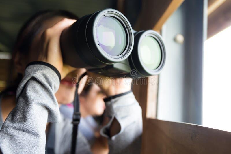 Uso asiático da mulher dos binóculos para birdwatching fotografia de stock royalty free