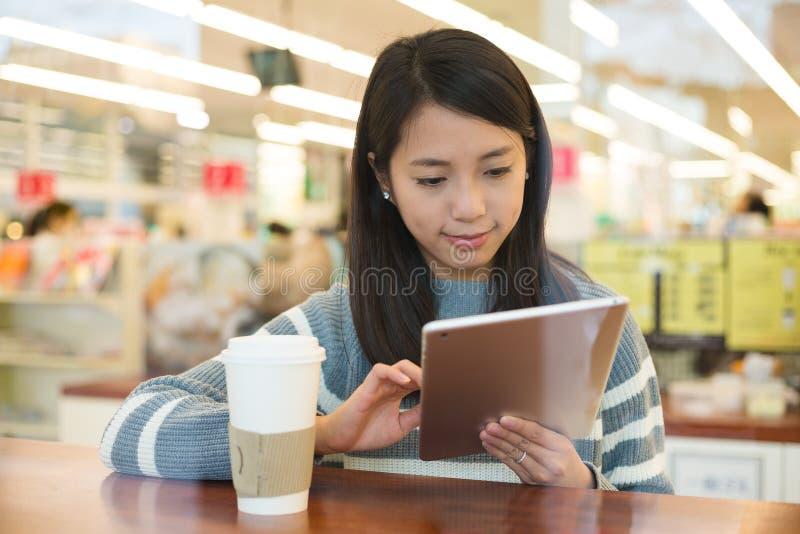Uso asiático de la mujer joven de la PC de la tableta con la taza de café imagen de archivo libre de regalías