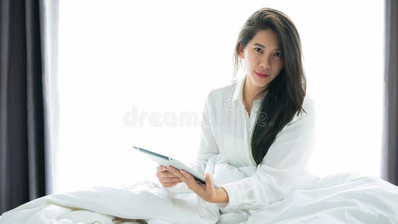 Uso asiático de la mujer que una tableta en la cama después de despierta en el MOR del fin de semana imagen de archivo