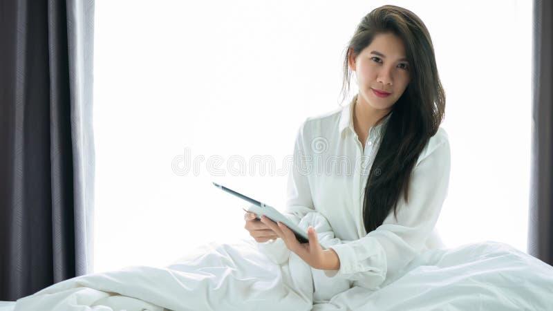 Uso asiático de la mujer que una tableta en la cama después de despierta en el MOR del fin de semana foto de archivo libre de regalías