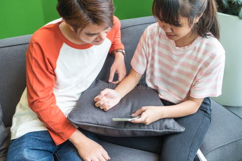 Uso asiático do adolescente e da menina móvel junto no sofá em casa T imagem de stock