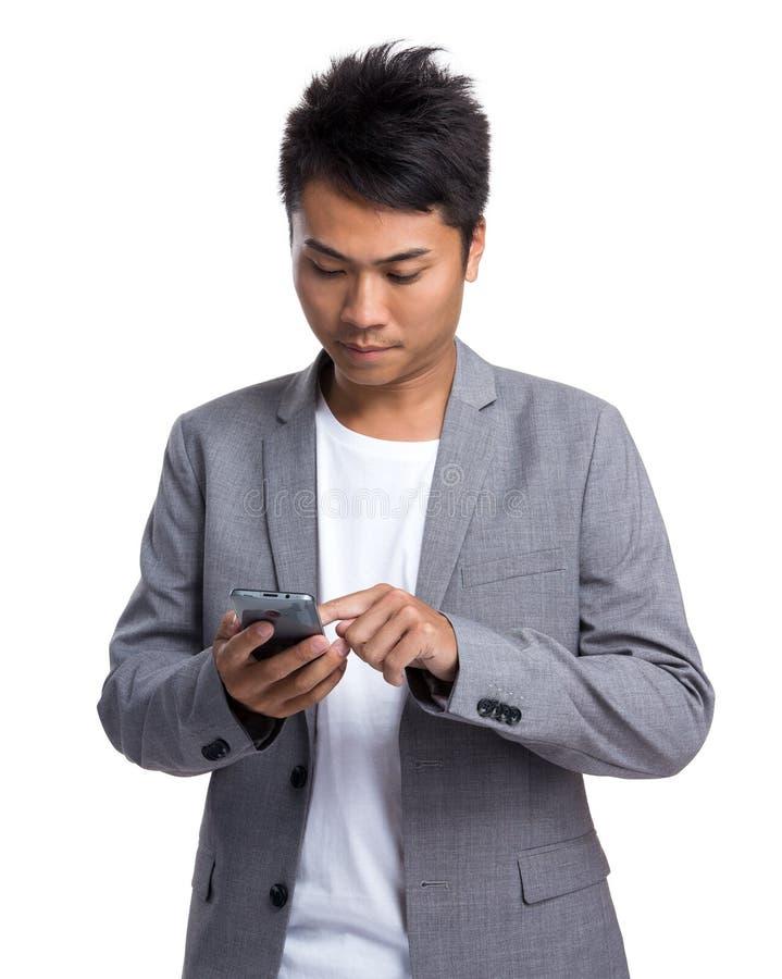 Uso asiático do homem de negócios do smrtphone imagem de stock royalty free