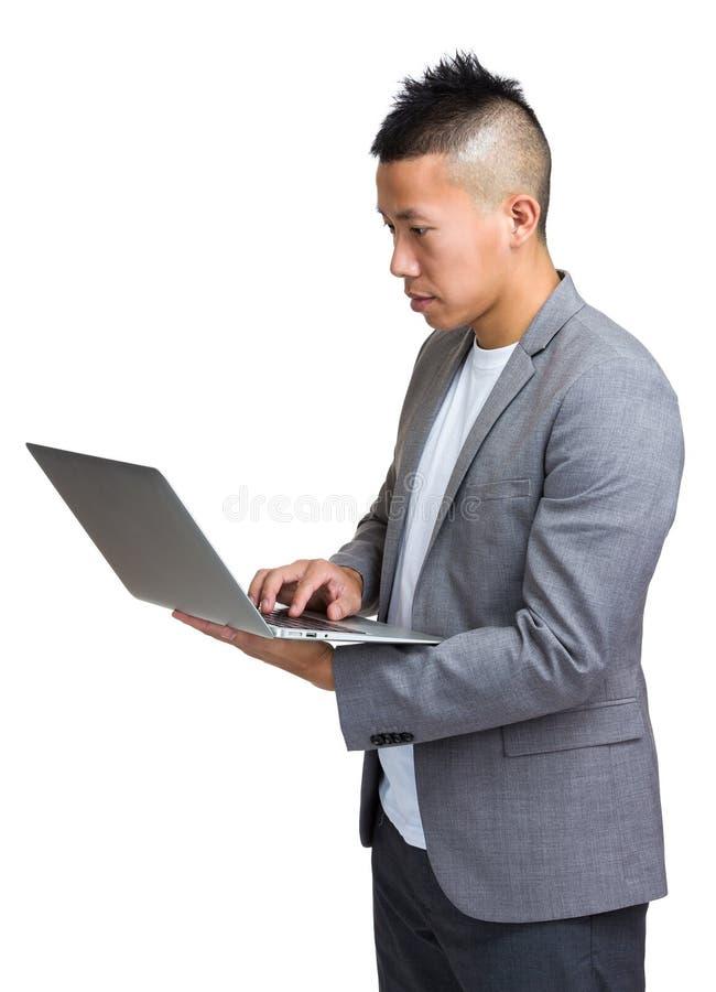 Uso asiático do homem de negócios do laptop foto de stock