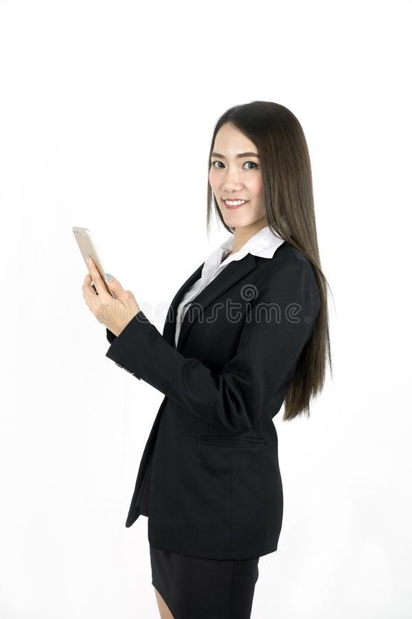 Uso asiático joven de la sonrisa de la mujer de negocios el teléfono móvil fotos de archivo