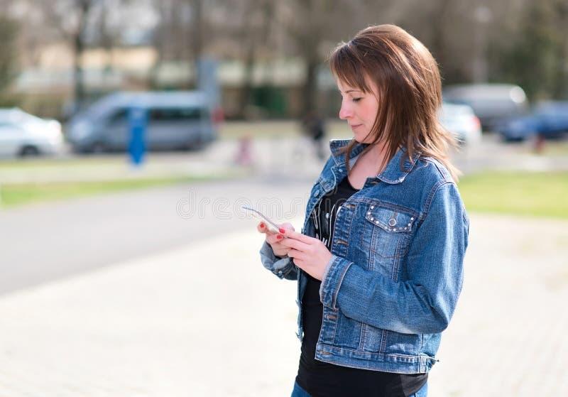 Uso bonito da mulher um telefone celular imagens de stock