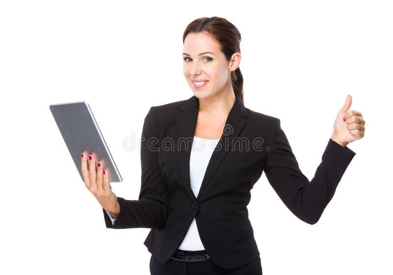 Uso da mulher de negócios da tabuleta e do polegar acima imagens de stock royalty free